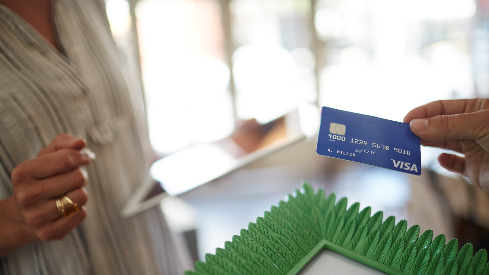 Person presenting Visa chip card as payment.