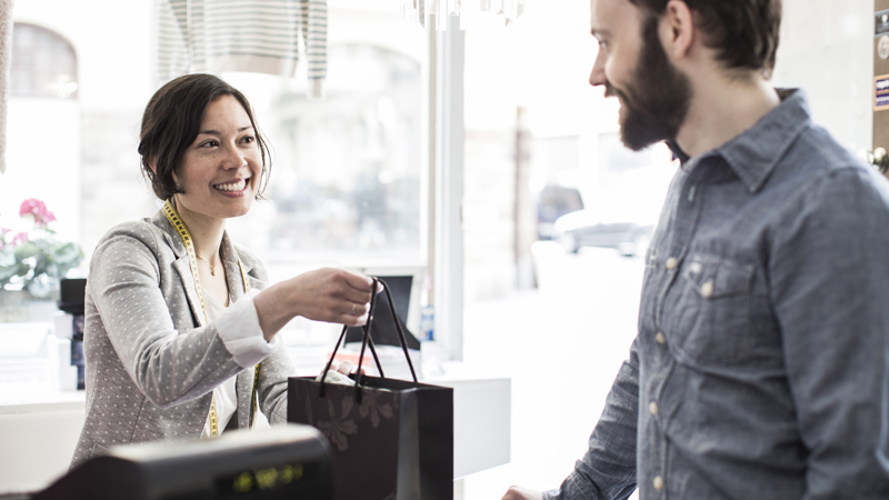 Woman handing over a paper bag to a man