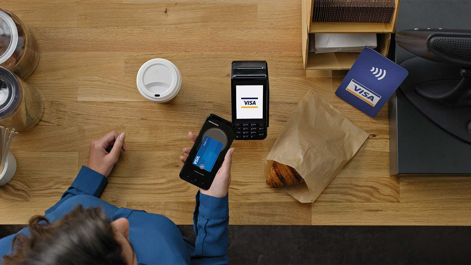 Customer paying for a purchase via a mobile phone using Samsung Pay.
